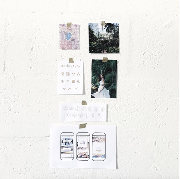 Print outs of photos, icons, ring and mobile website mockup taped on wall.